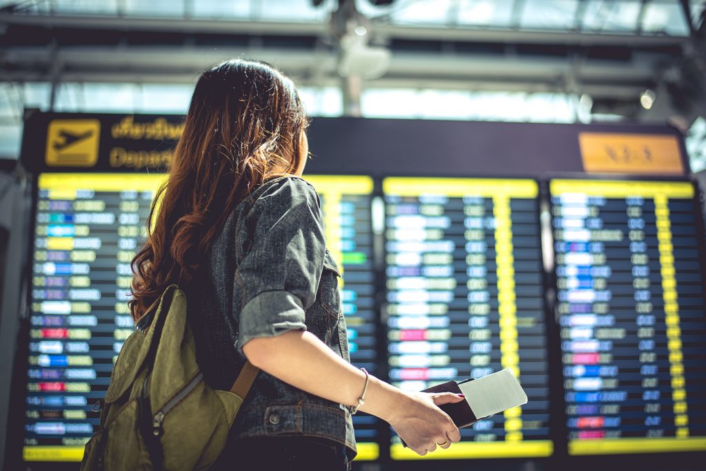 Beauty Female Tourist Looking At Flight Schedules For Checking T